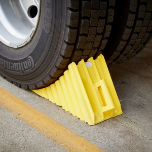 Yellow plastic wheel chock in use
